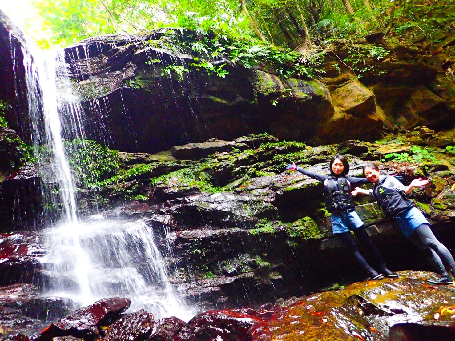 吹通川の滝の前でポーズをとる女性2人