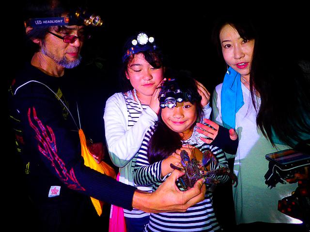 絶滅危惧種のヤシガニと記念写真を撮る家族