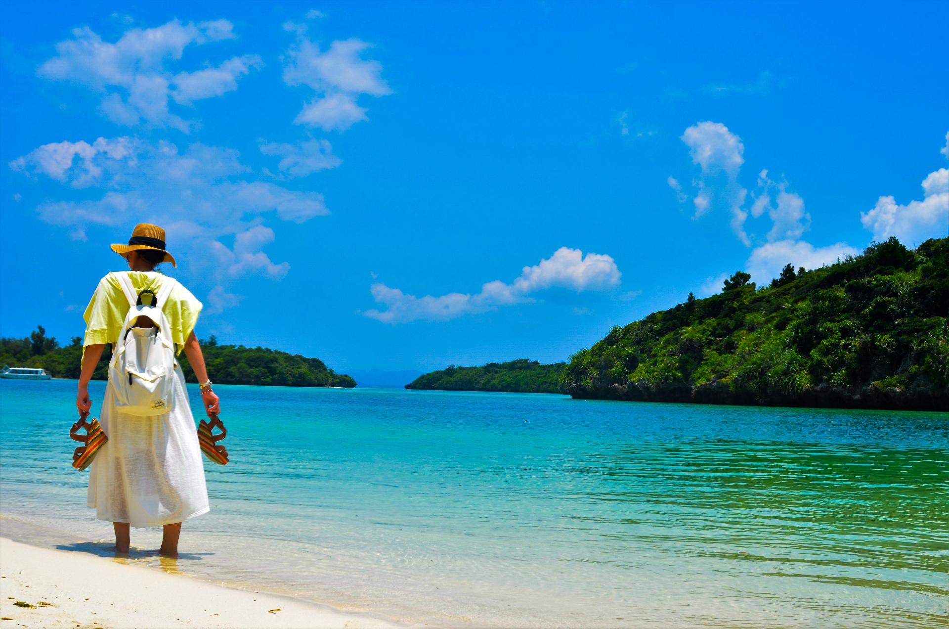 川平湾のビーチを散策する女性