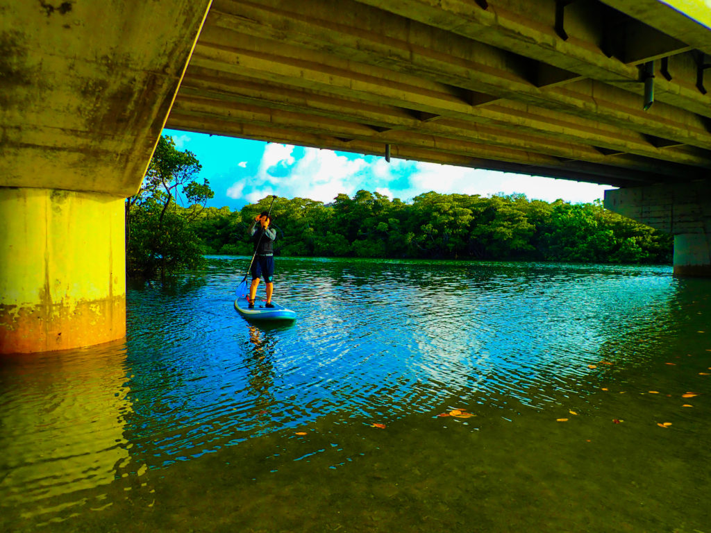 宮良橋の下でサップをしながらポーズをとる