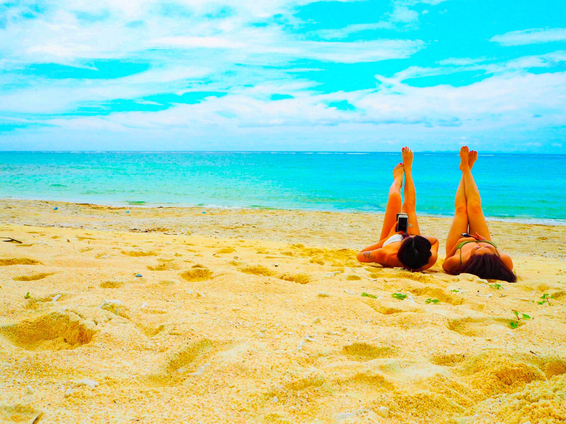砂浜に寝そべってポーズをとる女性2人