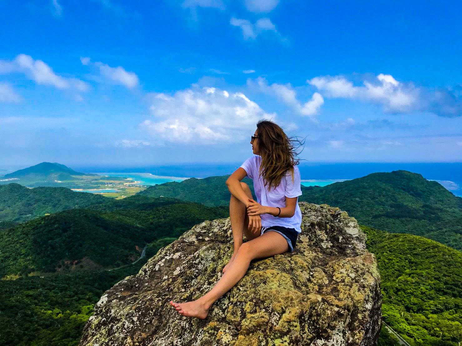 山頂の岩の上で休憩する女性