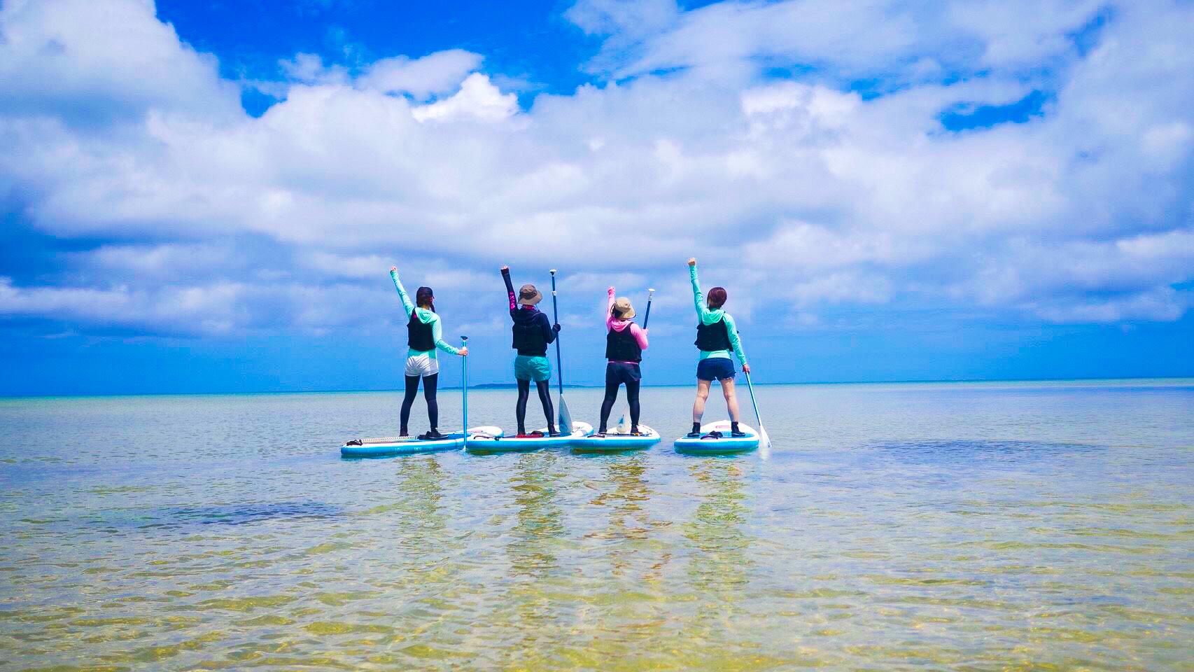 SUPに乗りポーズを決める女性グループ