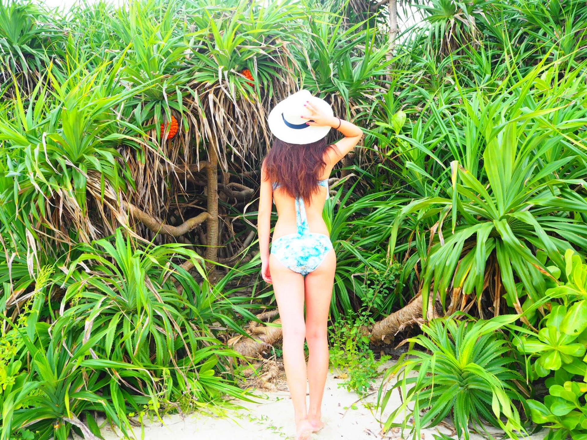 ビーチに立つ水着女性の後ろ姿