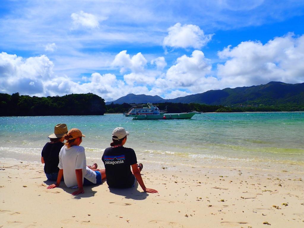 川平湾の砂浜に座る三人組