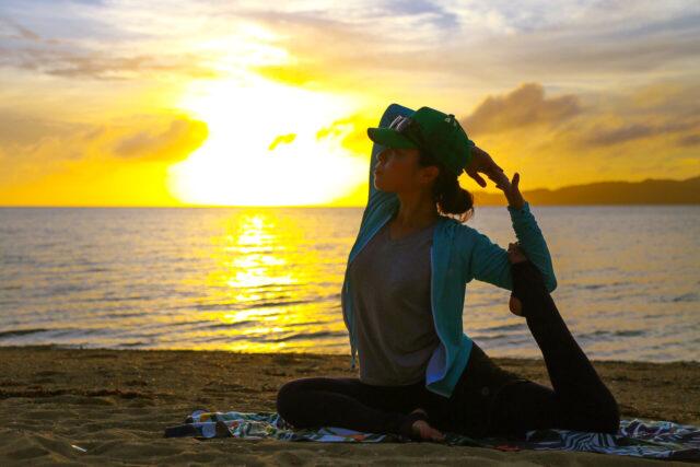 サンセットビーチヨガを楽しむ女性