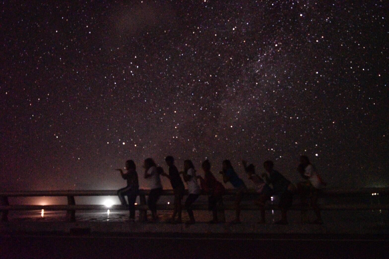 卒業旅行で星空を背景に写真をとる