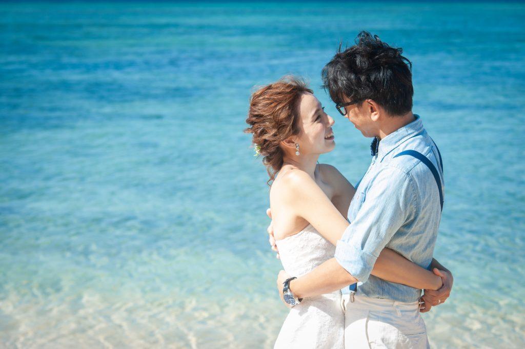 コバルトブルーの海をバックに抱き合うカップル