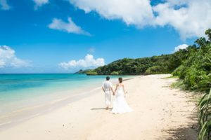 海辺をドレスで歩く新郎新婦
