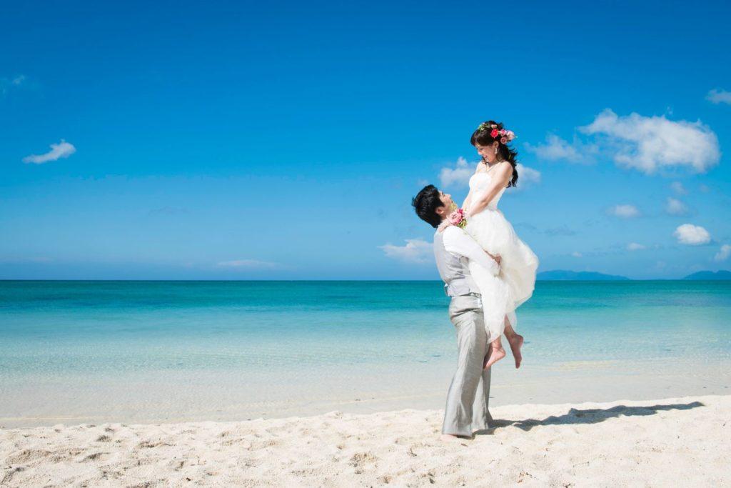 海辺で新婦を抱え上げる新郎